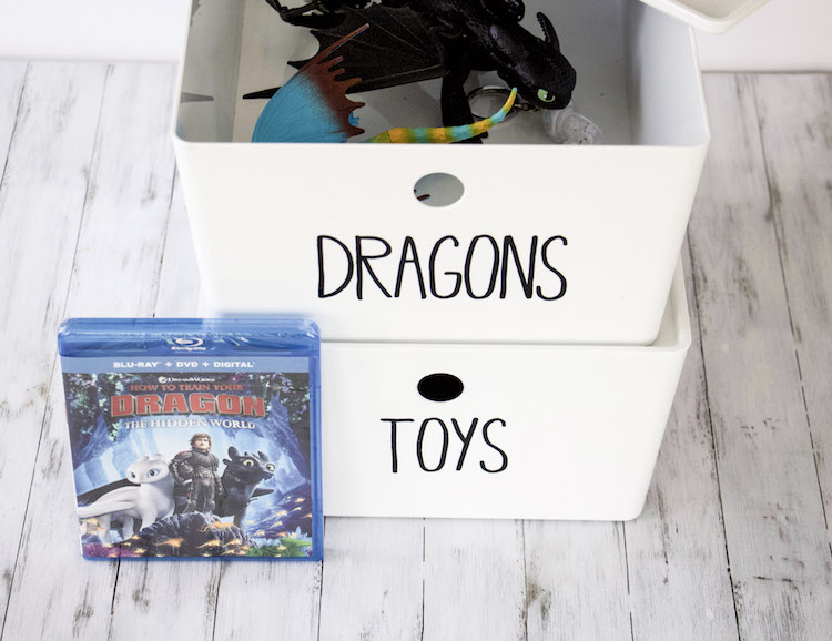 DVD of How To Train Your Dragon 3 next to two white bins with dragons from the movie inside