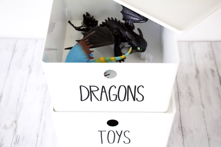 Two white boxes stacked on top of each other to demonstrate toy storage of action figures. Top bin is open to show dragons that coinsides with label on bin