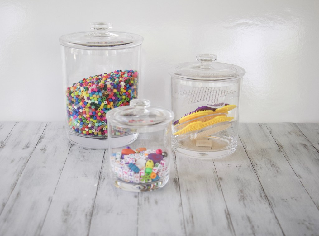 3 different size acylic canisters holding beads to demonstrate how to store pearler beads and other small bead supplies for kids #artorganization #shoplikeaprofessional