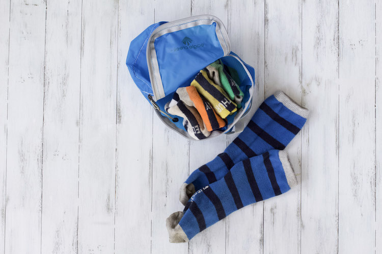 rolled up socks in packing cube next to pair of socks for travel packing list example