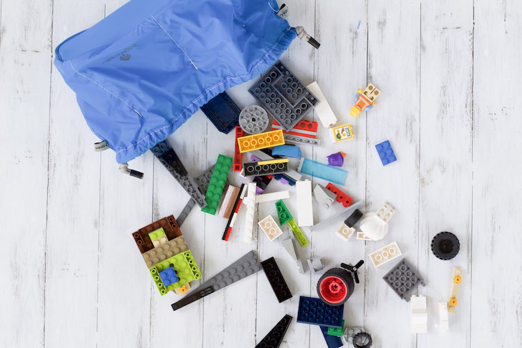 legos dumped out with cinch sac to demonstrate how to pack toys for traveling with kids