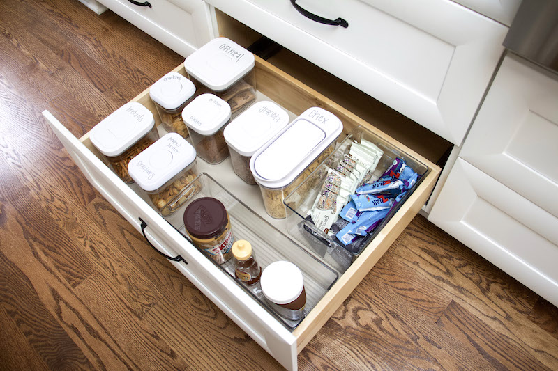 Kitchen drawer open with EasyLiners lining bottom and drawer organizers inside to keep drawers tidy
