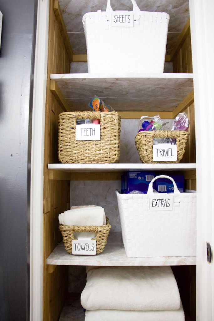 Folded towels and bins inside linen closet with marble shelf liner on shelves and back wall #linencloset