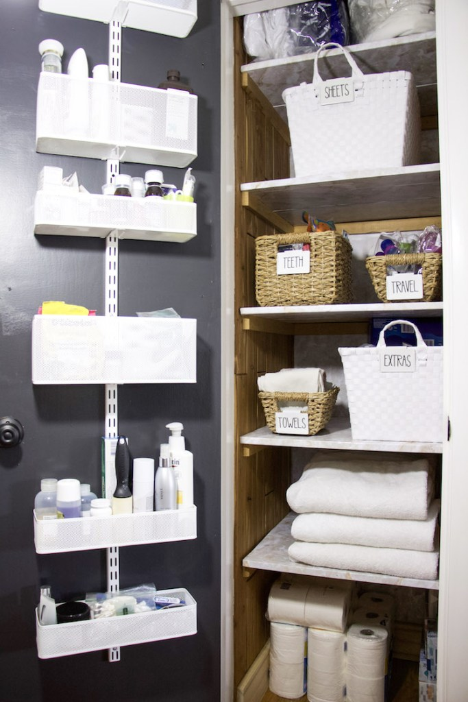 full shot of linen closet with items on door and items inside linen closet organized in bins with labels #linenclosets