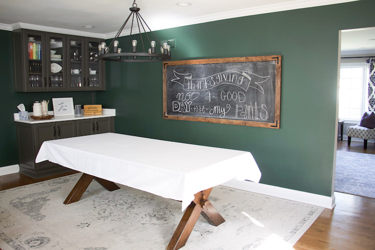 setting thanksgiving table decor with white tablecloth and chalkboard
