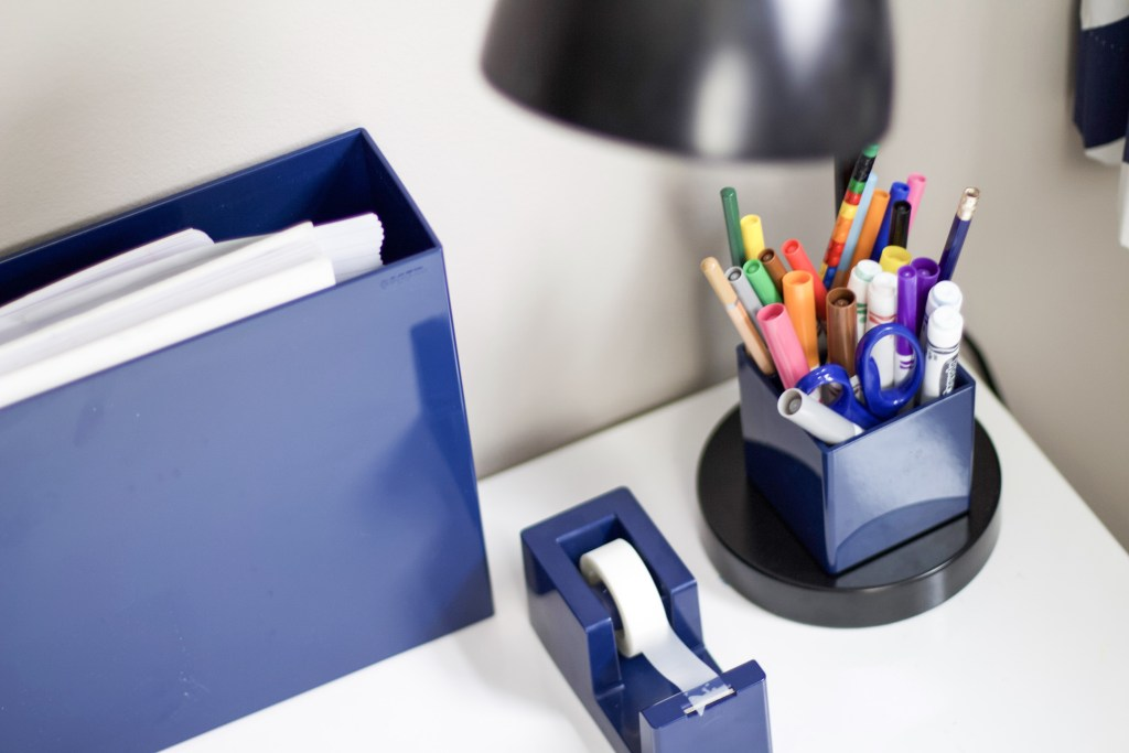 Desk with box of papers, tape, and pens to represent organizing for school #kidsorganizing