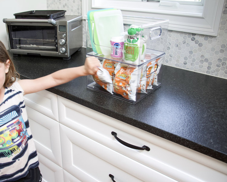 child reaching for snacks on countertop snack station