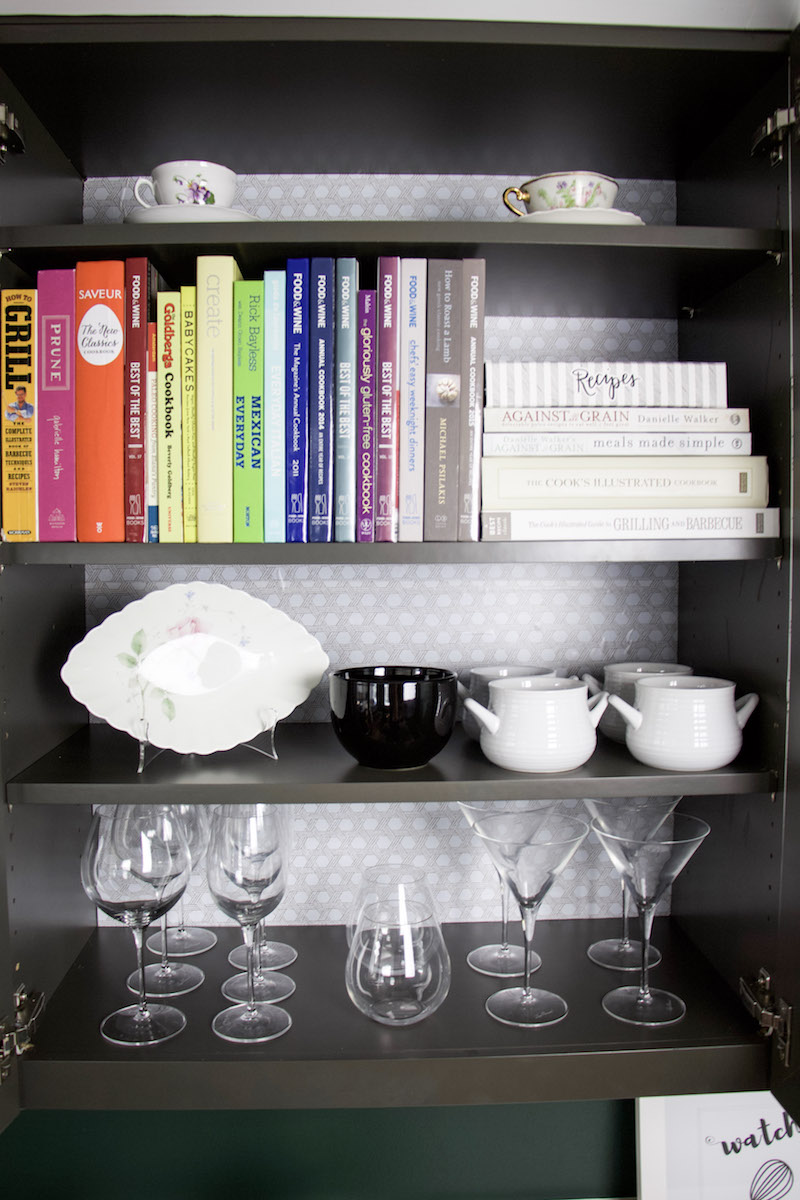 cabinet with cookbooks and bowls with basket weave easy liner on the back of cabinet