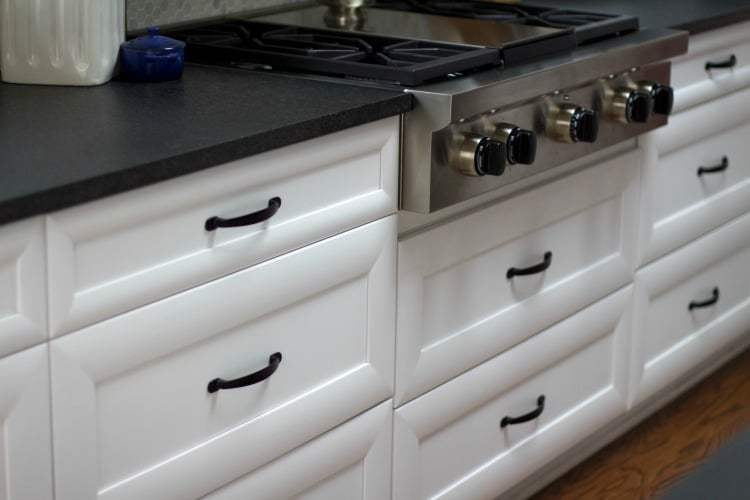 White kitchen cabinets and drawers with black countertop and hardware