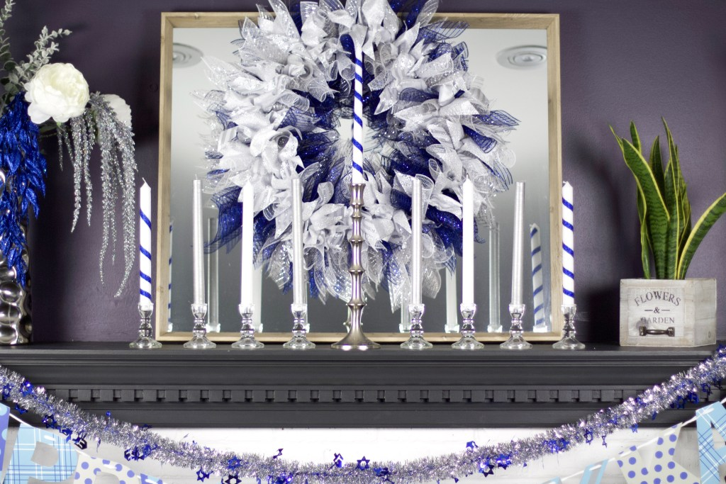 hanukkah wreath on mantel with candles as a menorah and flowers