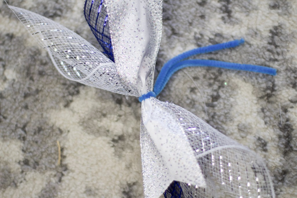 add pipe cleaner around the three pieces of rolled up deco mesh and ribbon to create hanukkah wreath