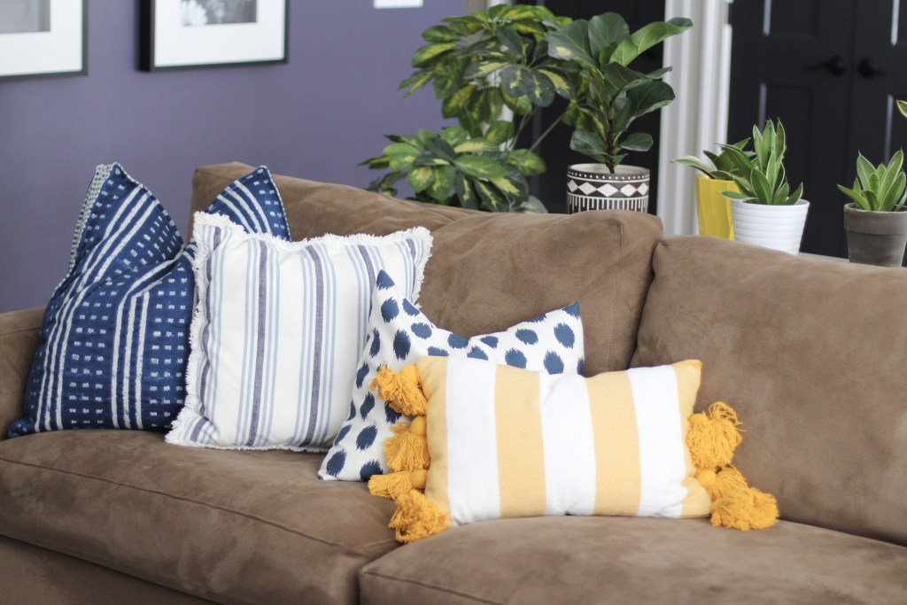 couch with blue and yellow pillows