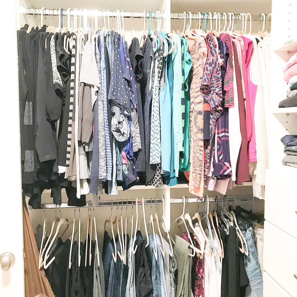 closet organized by color with shirts on top and pants on bottom