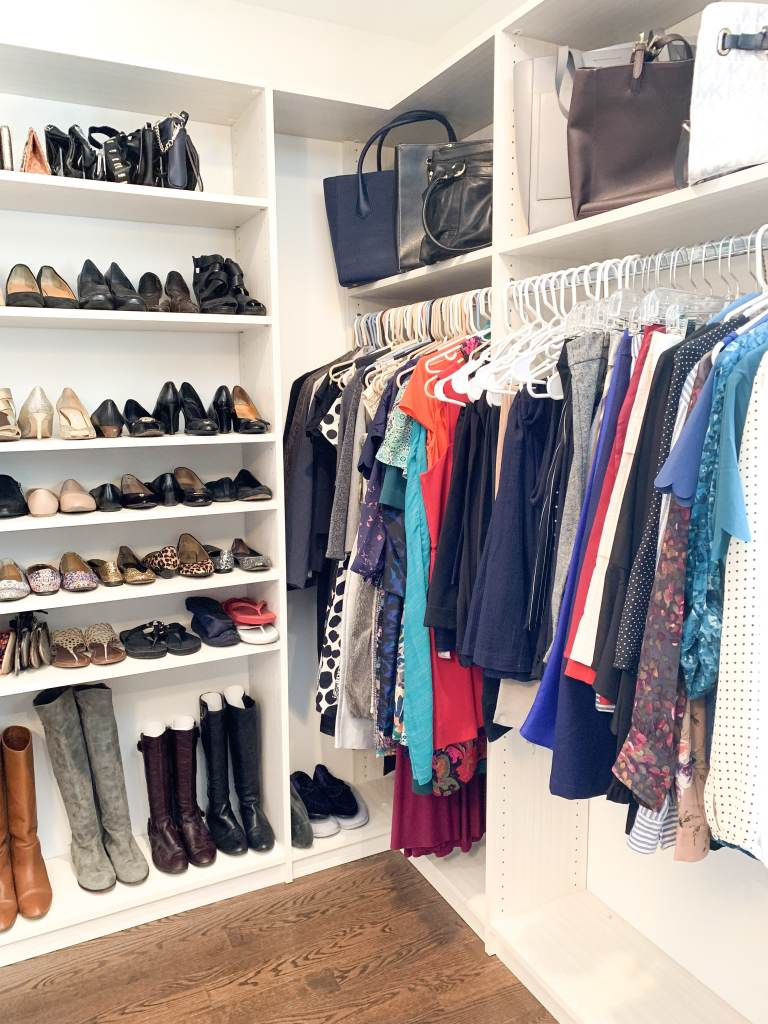 closet with shoes on shelves and dressed color coordinated