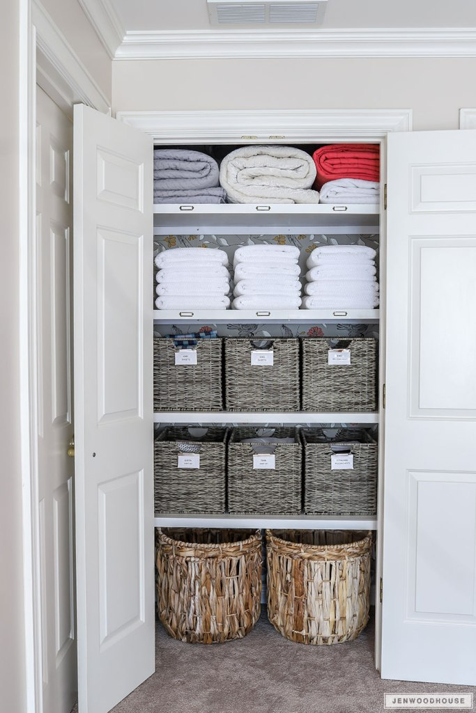 linen closet with baskets and white towels