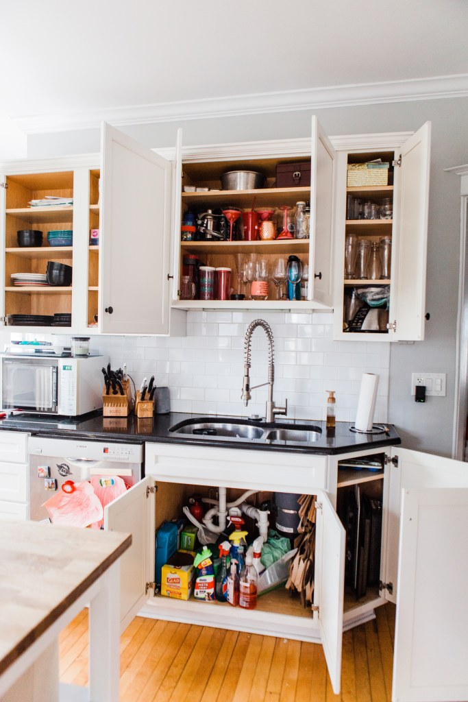 cabinets open above and below sink with disorganized shelves