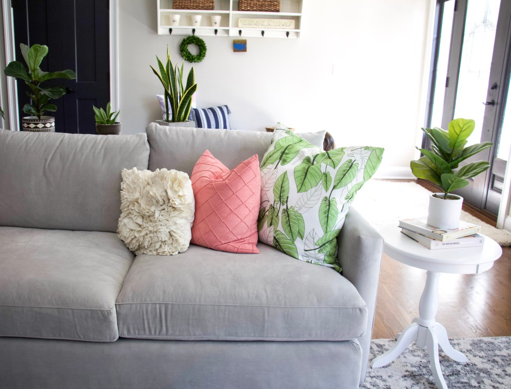 close up of pink and green chairs on grey couch