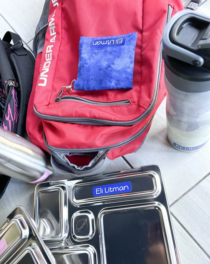 close up of red backpack with blue label on lunch box and water bottle