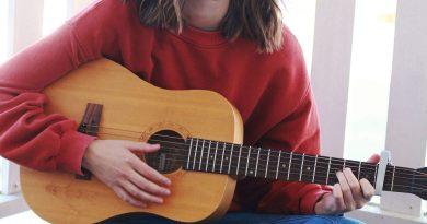 Justina Ward sitting with a guitar.