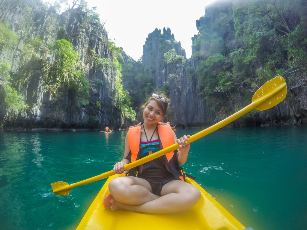 riding kayak in turquoise blue green water of small lagoon in el nido palawan