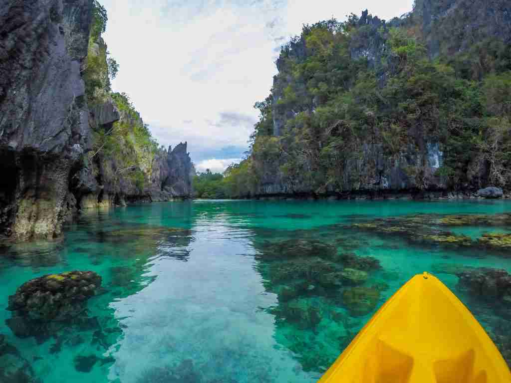 riding kayak in turquoise blue green water of big lagoon in el nido palawan