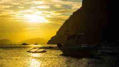 sunset view with boat in marimegmeg beach el nido palawan