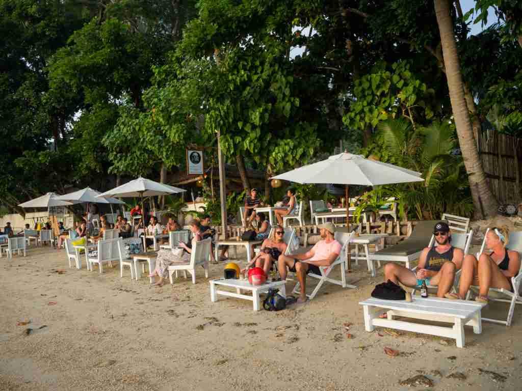 tourists chilling near the shore in marimegmeg beach el nido
