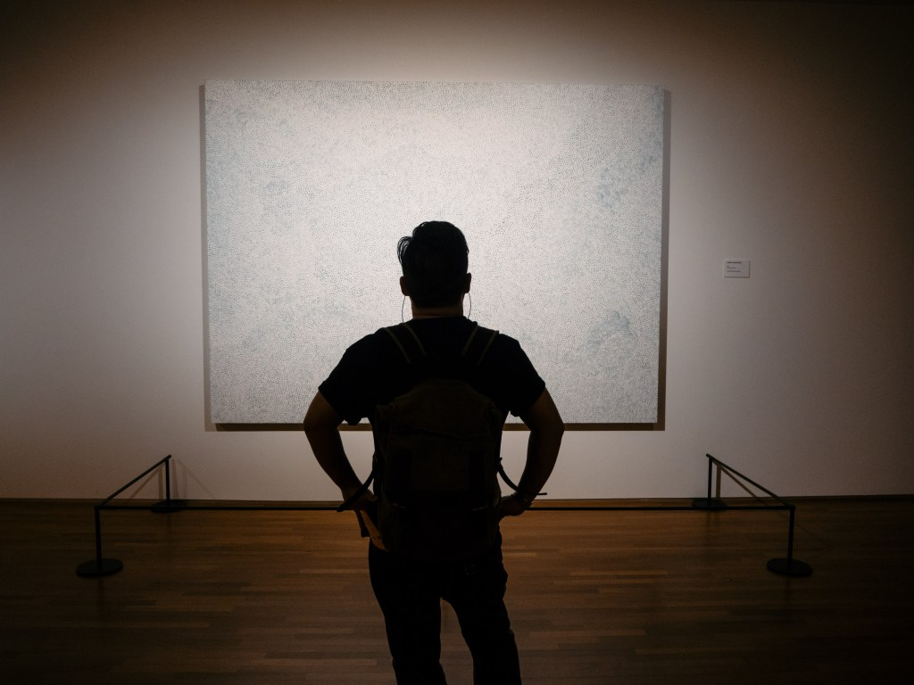 man silhouette in front of art of yayoi kusama in national gallery museum in singapore
