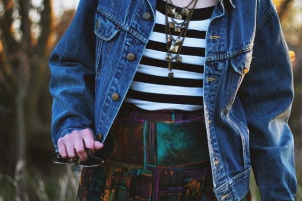 Striped top, colorful skirt, denim jacket, fake Doc Martens, and dark lips.