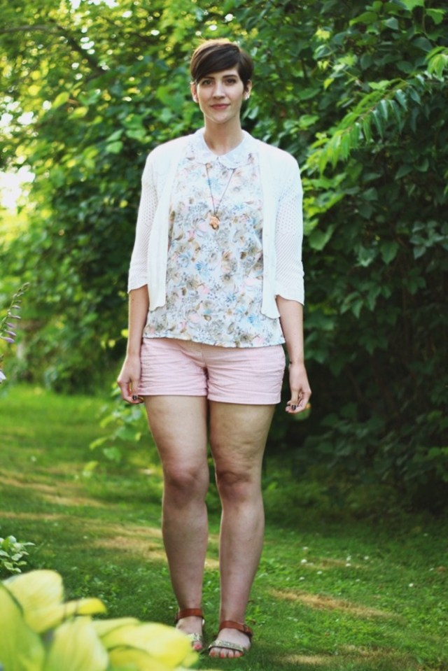 hannah is wearing a pastel floral peter pan collar blouse, a short white cardigan, red and white striped shorts, and glittery sandals. her hair is styled in a short pixie cut. she's standing in greenery.