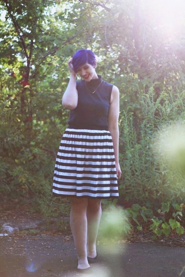 Outfit: Striped skirt, black sleeveless mock turtleneck, dainty gold necklace, black flats, purple pixie cut