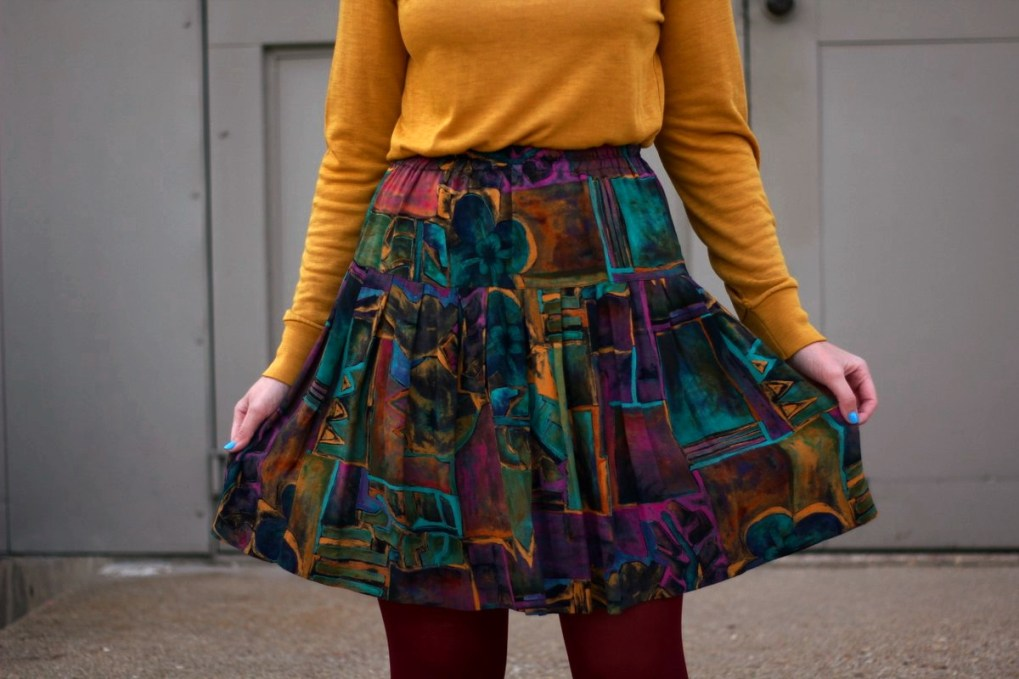 Outfit details: mustard yellow turtleneck, multi colored skirt, maroon tights