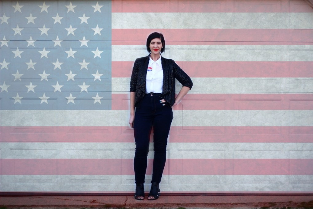 Election day outfit: American flag, white button up, red lipstick, I Voted sticker, black sequined blazer, high waisted jeans, black cutout heels
