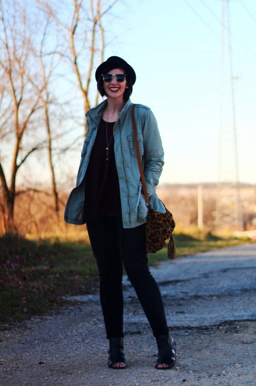 Outfit: burgundy top, burgundy lipstick, olive colored jacket, black sunglasses, pork pie hat, black jeans, Seven Dials Shoes, leopard print cross body purse