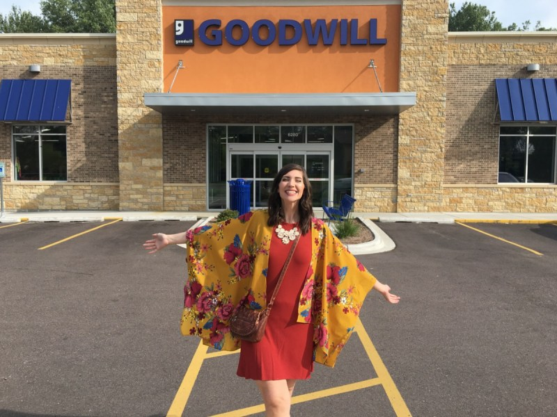 hannah rupp stands with open arms and a colorful outfit in front of an empty goodwill thrift store building