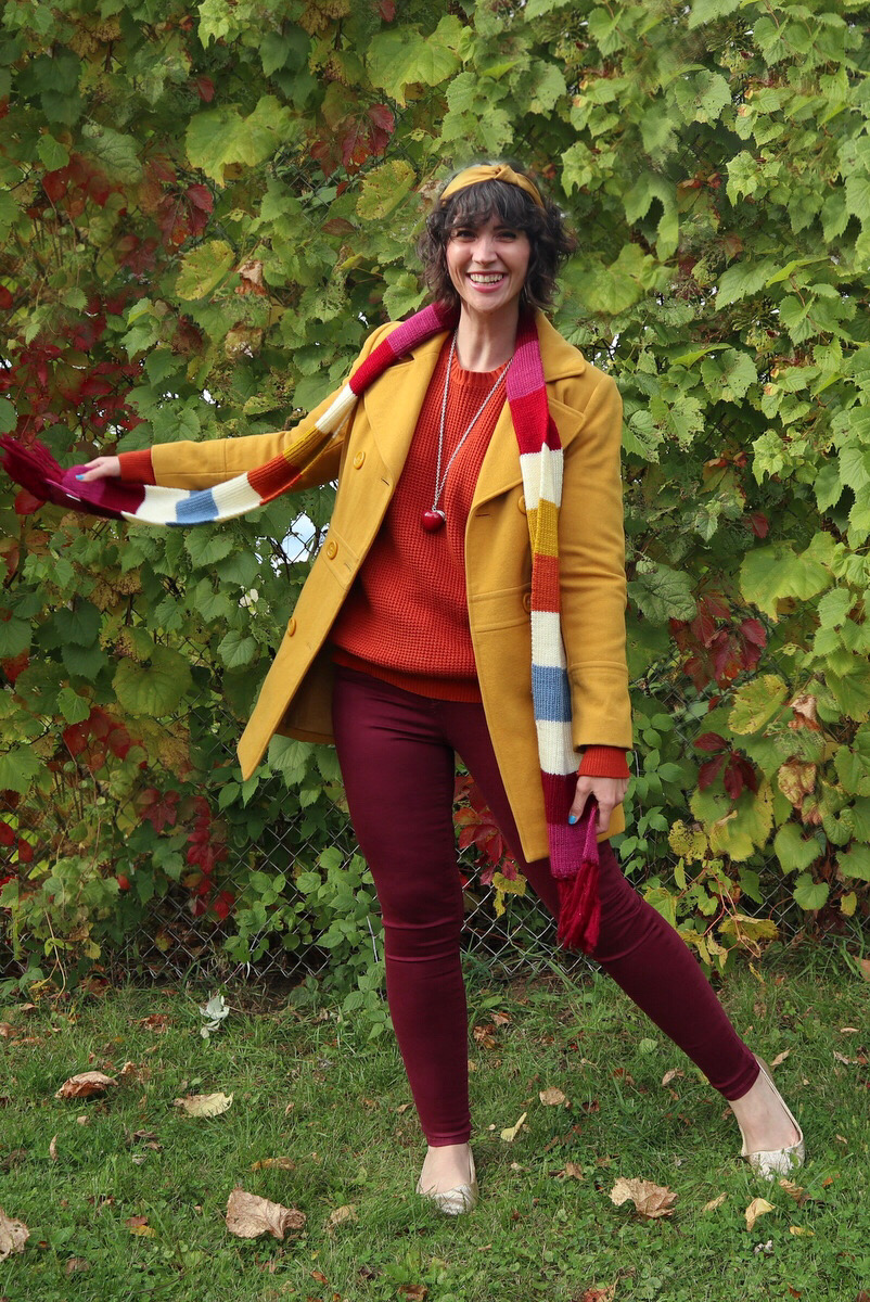 Hannah has short shaggy curls adorned with a yellow headband, in front of a leafy background, wearing an orange sweater, yellow jacket, striped scarf, and burgundy jeggings