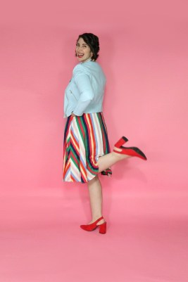 Hannah is wearing a thrifted graphic tee with a blue moto jacket on top, rainbow striped knee length skirt on the bottom, and red high heels
