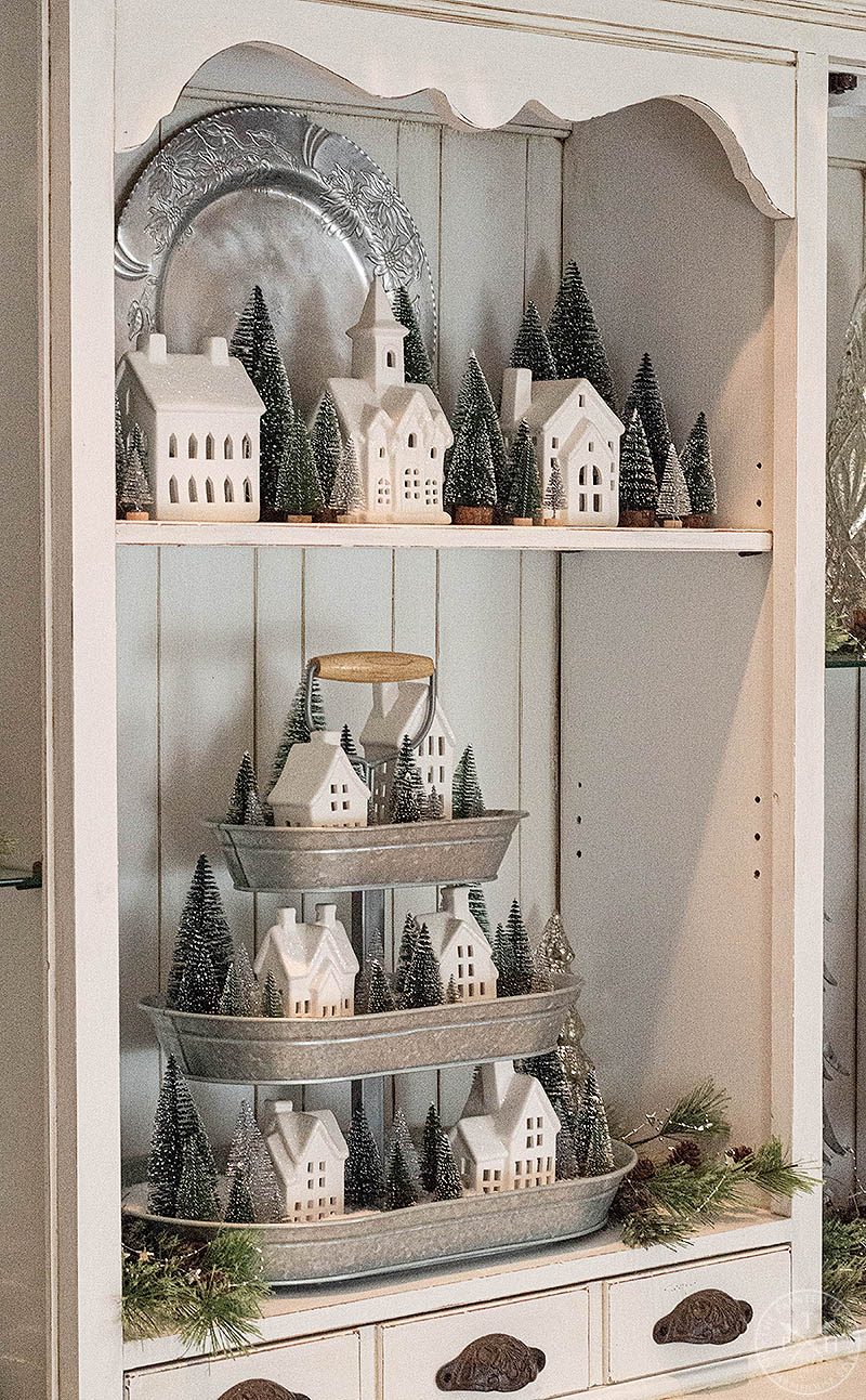 A Winter Hutch with a Christmas Village in a Tiered Tray