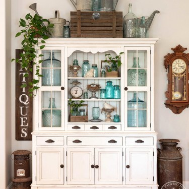 I decorated my hutch for spring using blue glass including mason jars, demijohn jugs and electric insulators! #farmhouse #masonjars #spring