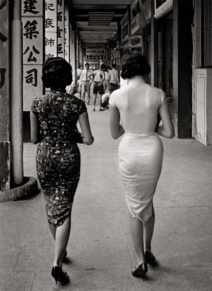 Women in tightly fitted qipaos walking down the street in Hong Kong in the 1950s; source unknown