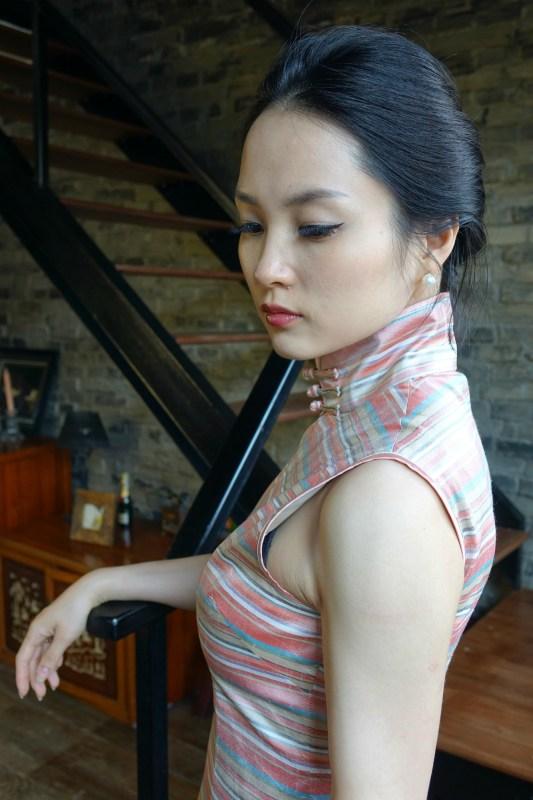 Wearing pink striped sleeveless qipao cheongsam left back view