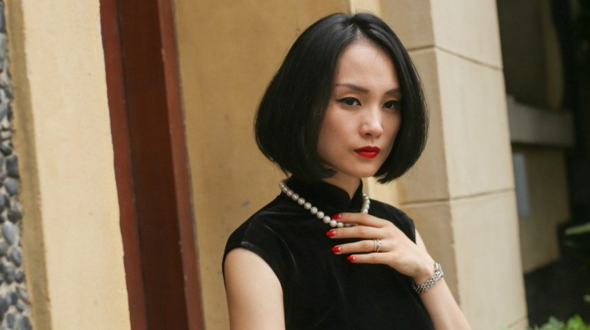 Miranda wearing black sleeveless velvet qipao and pearls