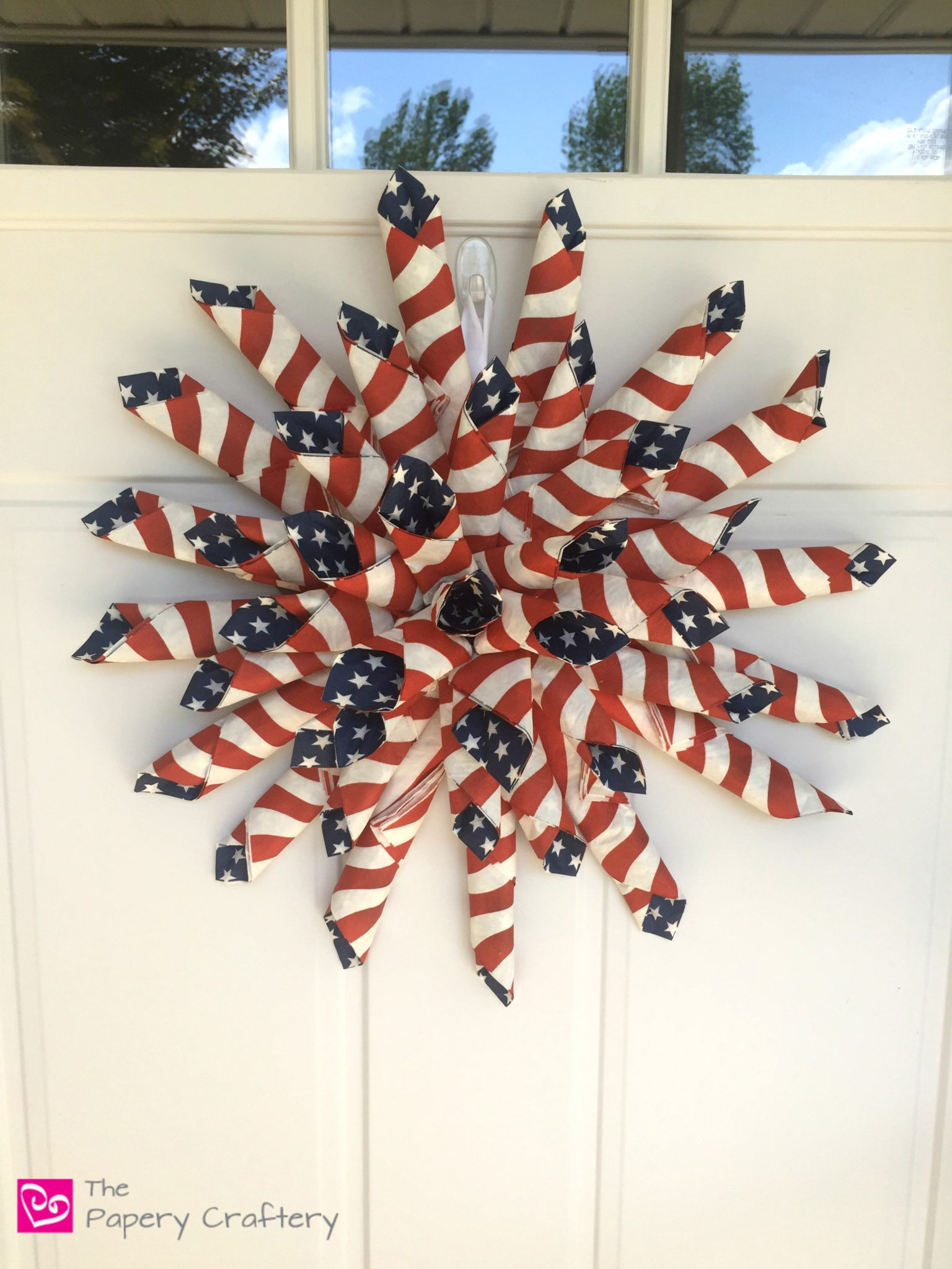 Patriotic Paper Wreath ~ Grab some flag napkins to whip up this red, white and blue stunner that can dress up your front door all summer long! || www.thepaperycraftery.com