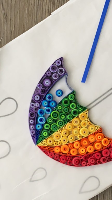 Partially filled in rainbow umbrella made from quilling paper and quilling tools