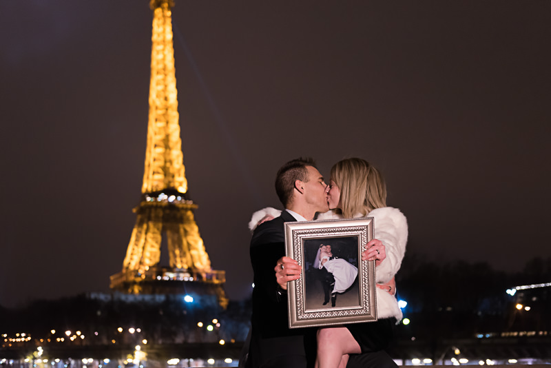 couple-holding-their-wedding-photo-at-the-eiffel-tower-and-kissing