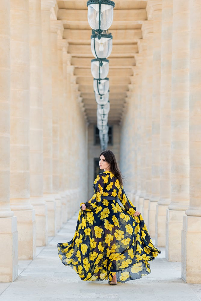Beautiful girl dressed in yellow running between the columns of Palais Royal in Paris