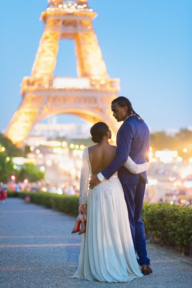 Paris night photo of bride holding her nude Christian Louboutin heels and walking to the Eiffel Tower