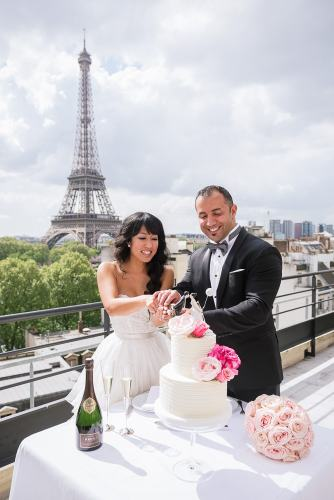 Bride and groom cutting wedding cake on Shangri La terrace with Eiffel Tower in the background