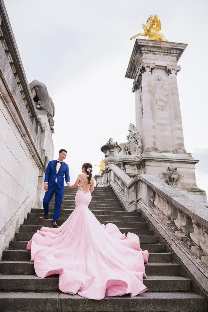 Paris pre wedding photographer - asian bride with huge pink dress posing on the Alexander 3 bridge