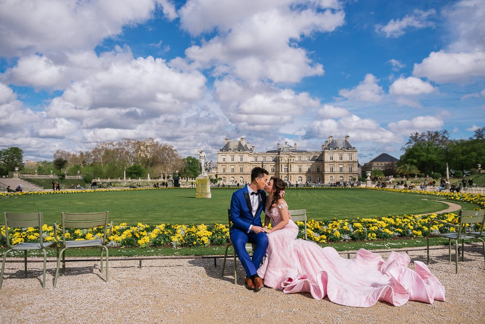 Blue sky, white clouds, Luxembourg gardens casstle and pre wedding couple with rich pink dress kissing